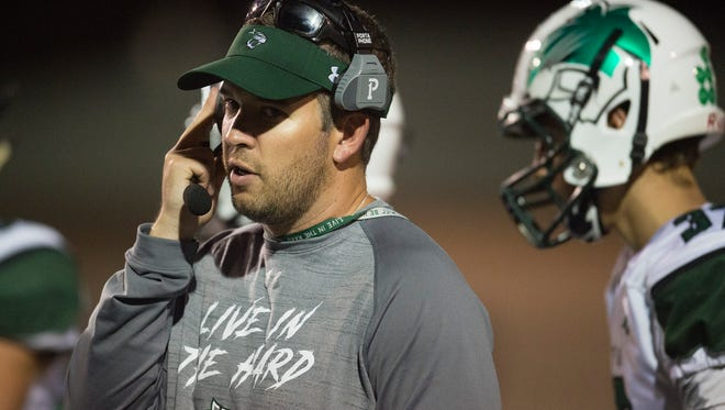 Fossil Ridge High School coach Zak Bigelow talks on his headset during a game against Poudre at French Field on Friday, September 15, 2017.