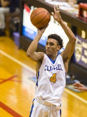 Carmel High School senior Eddie Gill (4) puts up a