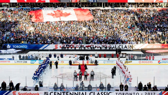 The Toronto Maple Leafs and the Detroit Red Wings line up for the national anthems before the NHL Centennial Classic hockey game in Toronto on Sunday, Jan. 1, 2017. (Nathan Denette/The Canadian Press via AP)