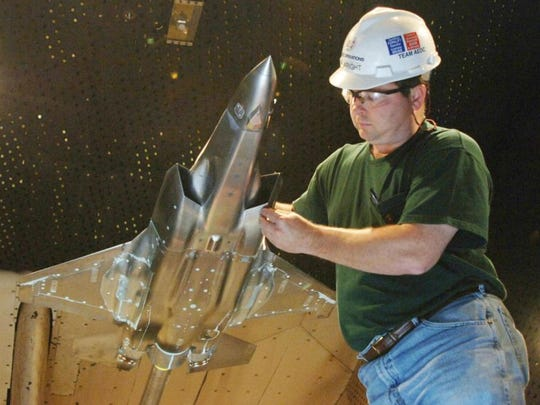 Tim Wright examines an F-35 Lightning II   model in the Arnold Engineering Development Center's 16-foot transonic wind tunnel at Arnold Air Force Base near Tullahoma.