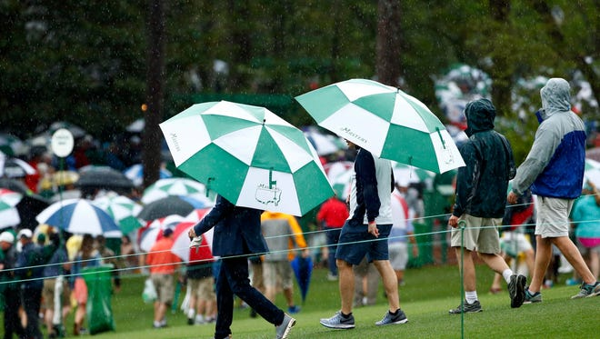 Patrons exit the course as thunderstorms move in during a practice round at the Masters at Augusta National on April 3.