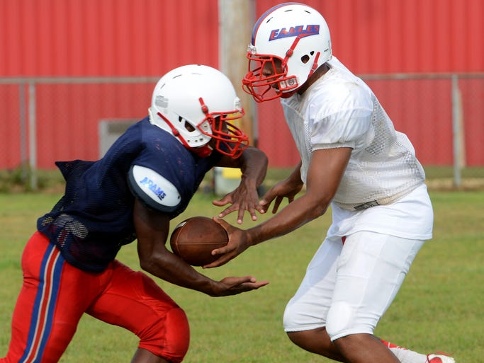Pine Forest High School quarterback Danny Jackson hands off the ball to running back Dejon Brown Tuesday while preparing for the 2014 kickoff.