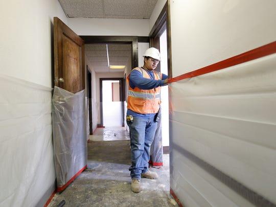 Ivan Saucedo of Dantex Construction prepares for asbestos abatement at the Bassett Tower in Downtown El Paso. Demolition of the building's interior began in July.