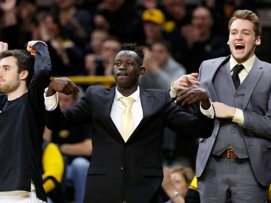 Iowa guard Peter Jok, center, celebrates on the bench