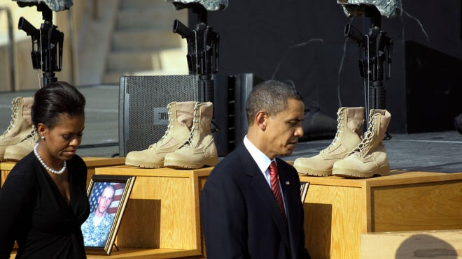 President Obama and first lady Michelle Obama file past fallen heroes crosses at a memorial for victims of the first Fort Hood shooting in 2009.