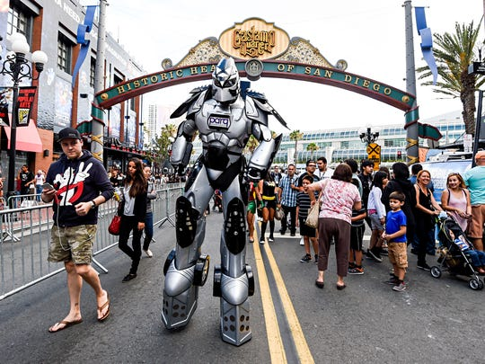 A fan in a huge robot costume towers over sightseers in the Gaslamp District on first day of the 2015 Comic-Con International held at the San Diego Convention Center Thursday, July 9, 2015 in San Diego.  The pop-culture event runs July 9-12.  (Photo by Denis Poroy/Invision/AP)
