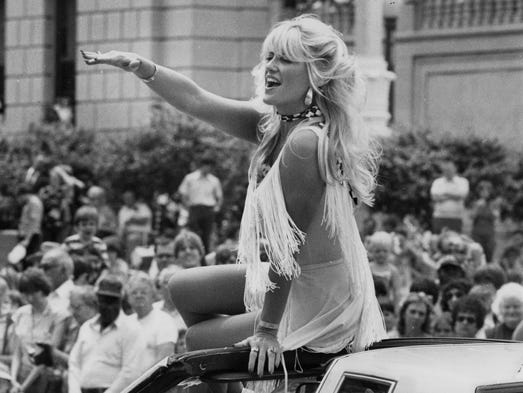 Linda Vaughn, again incorporating the unconventional windshield-seated approach to parading around in a convertible. 500 Festival Parade, Indianapolis May 28, 1981.