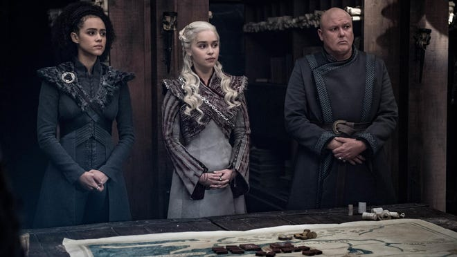 """This image released by HBO shows from left, Nathalie Emmanuel, Emilia Clarke and Conleth Hill in a scene from """"Game of Thrones,"""" that aired Sunday, May 5, 2019. """"Game of Thrones"""" fans got a taste of the modern world as the fictional series winds down to its final episodes. Eagle-eyed viewers Sunday spotted a takeout coffee cup on the table during a celebration in which the actors drank from goblets and horns. Daenerys and Jon did not react to the out of place cup. (Helen Sloan/HBO via AP)"""