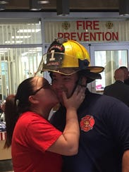 Firefighter Edgar Quintana of Station 1 is kissed by