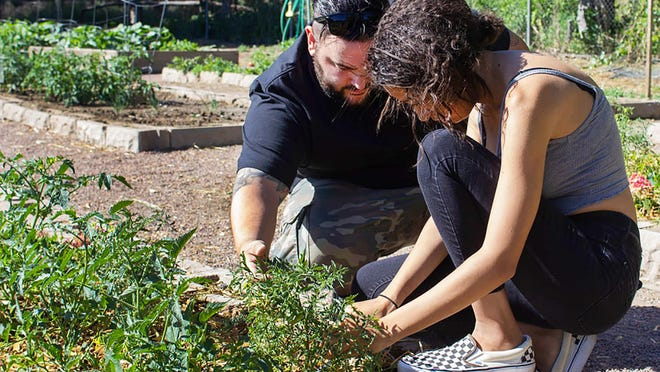 Ian Norris of the Green Thumb Initiative works with a student in the community garden in Canon City.