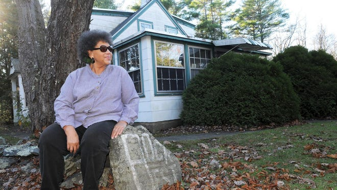 Valerie Cunningham sits on the stonewall at Rock Rest in Kittery Point, Maine, which was a popular destination for vacationing African Americans. She worked there for two years as a young girl.