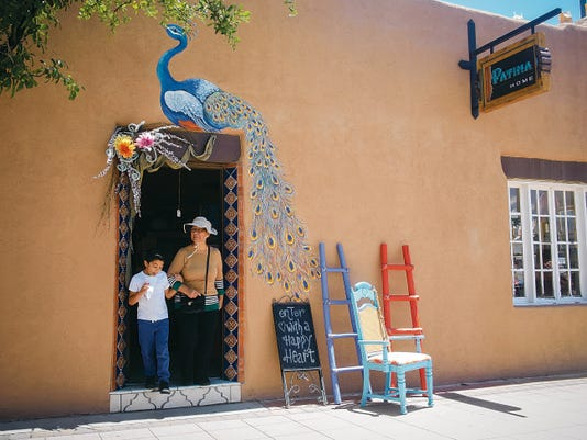 Jett Loe--Sun-News   Visitors exit Patina, the new home decor shop in downtown Las Cruces, on Saturday during the Farmer's Market. Market.