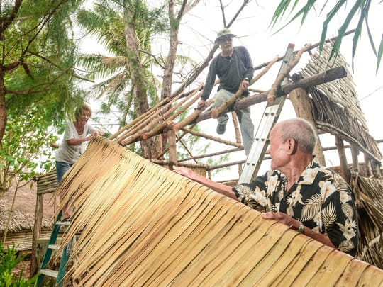 Clockwise from left, crafter Rosita San Nicolas, maintenance worker Paul Naputi and site manager Carlos Paulino demonstrate how a section of thatch, made from nipa palm leave, is hung on the rafters of a Chamorro hut at the Gef Pa'go Chamorro Cultural Village in Inarajan on Thursday, Jan. 7.