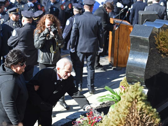 John J. Falcone, father of late City of Poughkeepsie Detective John M. Falcone lays a flower at his son's memorial in the City of Poughkeepsie following a ceremony to commemorate the fifth anniversary of Detective Falcone's death on Thursday.