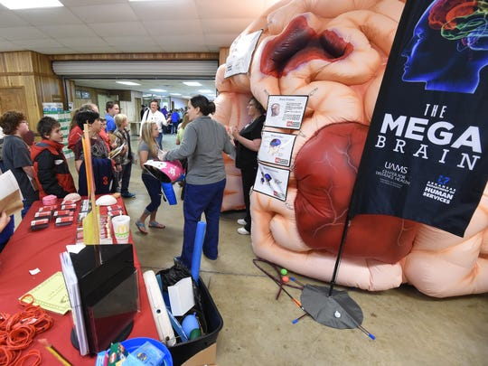 Sixth graders from Pinkston Middle School gather Wednesday, Feb. 24, 2016 around the Mega Brain at the Baxter County Fairgrounds during the annual CSI Project.