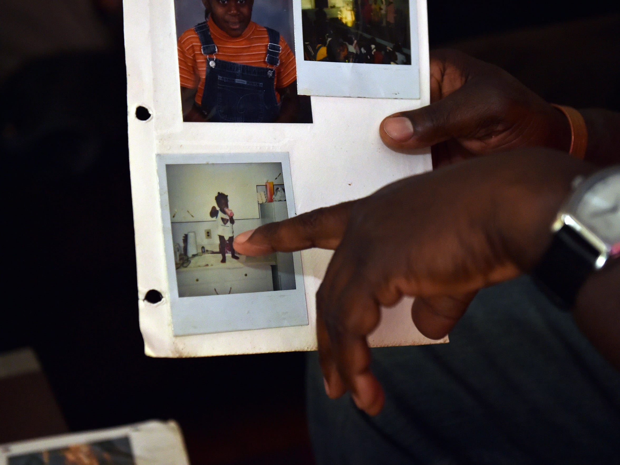 Melvin Mangum Sr. points to a photograph of his son,