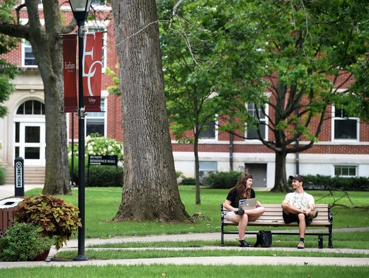 Students talk together on a bench around the Heart on Aug. 24, 2016, at Earlham College in Richmond.