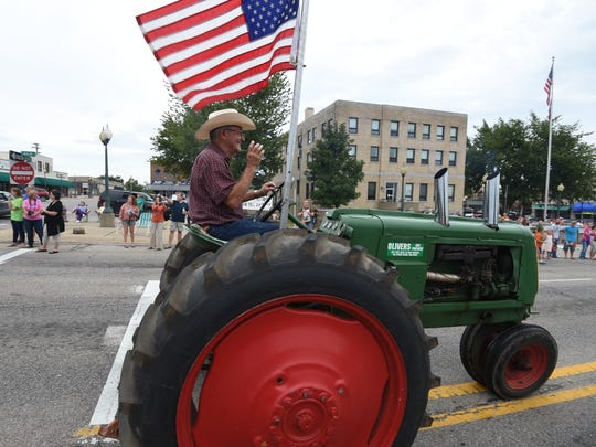 A classic tractor bearing the nation's flag rolls past the square in Mountain Home Wednesday during the annual Baxter County Fair Parade.