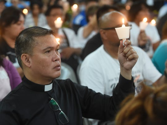 A religious figure is joined by fellow memorial attendees in holding up candles for suicide victims during the 12th Annual Lifeworks Guam Candlelight Memorial Service in 2016.