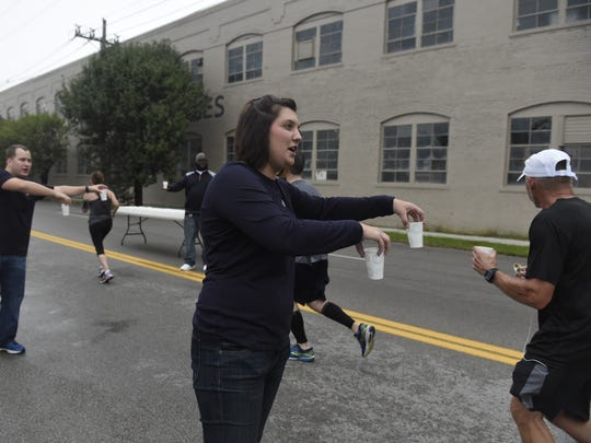 Kristine Hass of Evansville holds cups of water for runners as they pass by Bosse Field during the Evansville Half Marathon in Evansville Saturday.