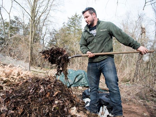 Tony Campisi uses a pitchfork to rearrange a compost