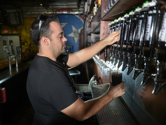 Wesley Keegan, owner Tailgate Beer Brewery, pours beer