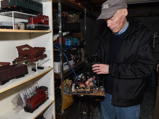 Thomas Murphy goes through his train collection in the basement of his Hyde Park home. Murphy has been involved with the garden railway hobby for 24 years.