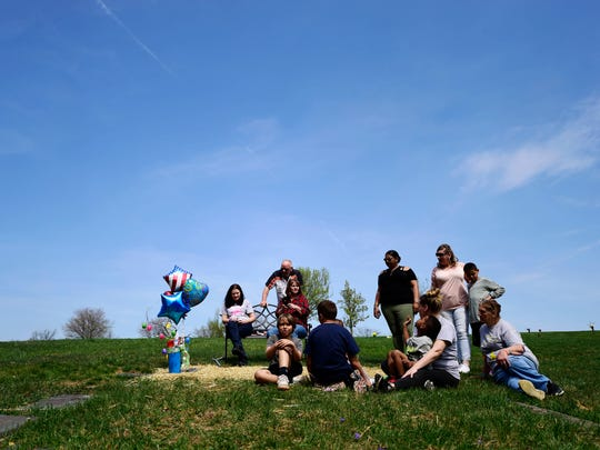 Jen Zeigler, left, sits at the gravesite of her son, Ayden Zeigler-Kohler, surrounded by his grandparents, cousins and aunts at Mount Rose Cemetery in Spring Garden Township on April 15. They decorated his temporary marker for Easter, their first holiday since Ayden died.