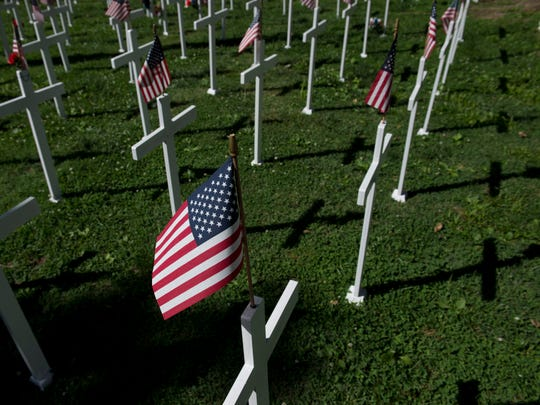 White crosses and American flags dot the lawn at the Central Park Memorial Day display.