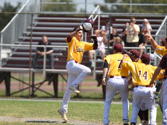 Pete Grasso is mobbed at home plate by teammates after a home run in the CAC playoffs.
