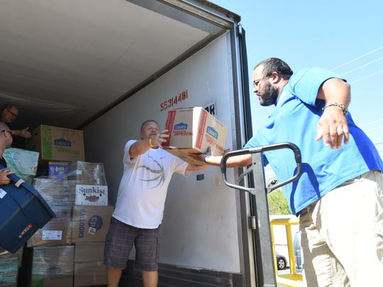 A group of men load a semi-tractor trailer with different types of items Thursday morning at Christ Community Church. The church collected items for victims of Hurricane Harvey.