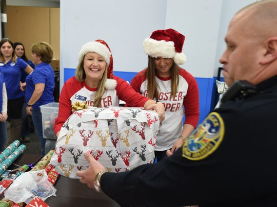 Mountain Home Junior Auxiliary President Kristen Wooldridge smiles Saturday as she hands Sgt. Brian Corbett of the Mountain Home Police Department a wrapped present during the annual Shop With a Cop event.
