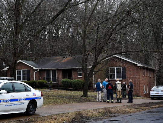 Investigators inspect the house where three people