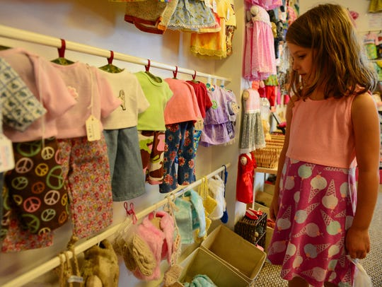 A young girl checks out the clothing at The Doll Clothes