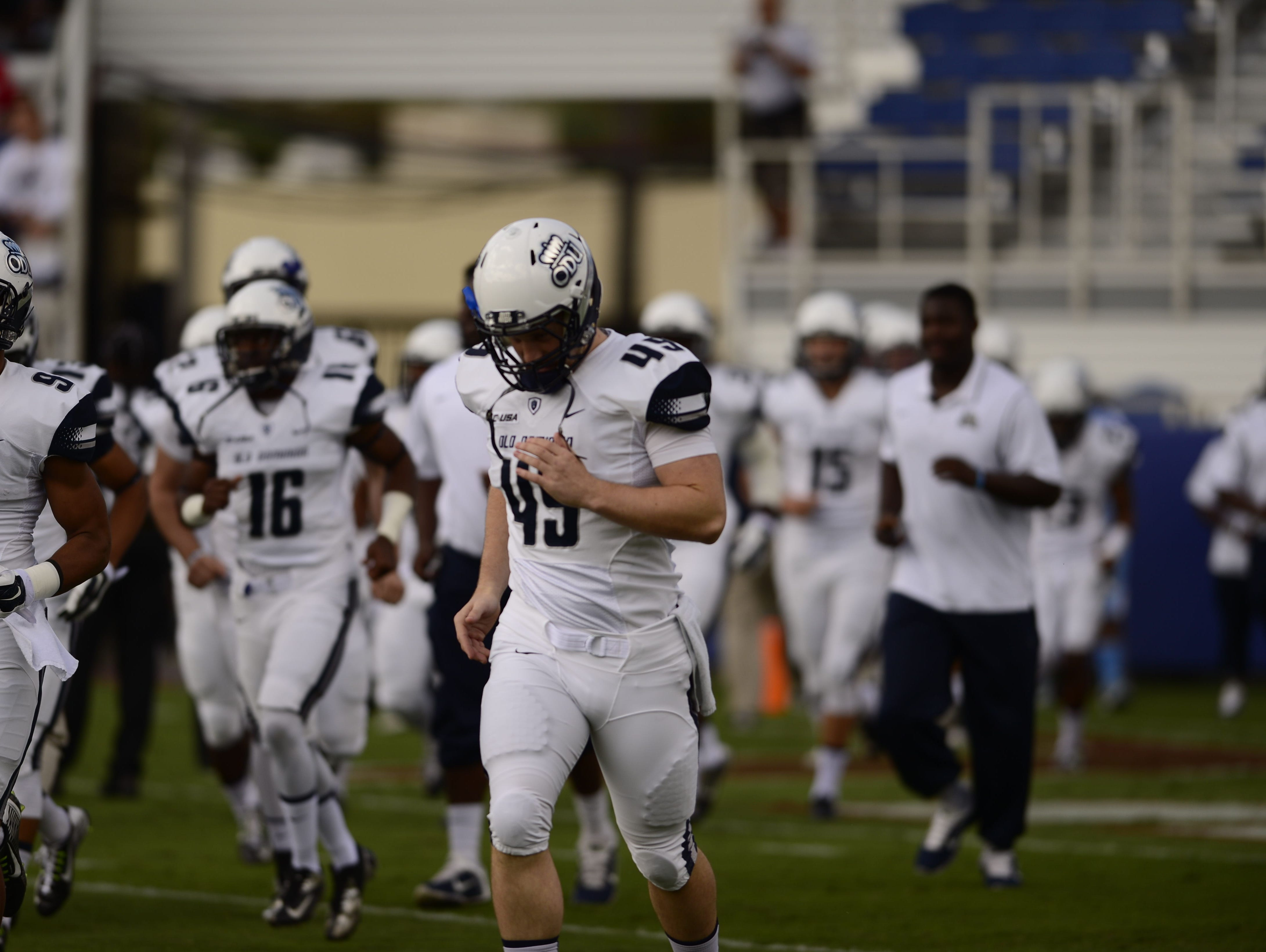 Rick Lovato Jr. of Middletown makes his way out onto the field with his Old Dominion teammates last season.