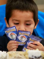 Alfred Padilla, 4, gets distracted from his meal by Pokémon cards on Thursday at the Farmington Civic Center.