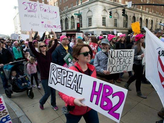 """Protesters march up Fayetteville Street during the annual """"Historic Thousands on Jones Street"""" (HKonJ) march in Raleigh, N.C., on Saturday, Feb. 11, 2017. The rally was organized to express support for the Affordable Care Act, opposition to President Donald Trump's plans to build a wall along the border with Mexico and his executive order on immigration."""