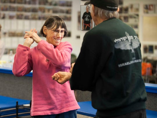 Israeli Krav Maga of Cherry Hill teaches women how to be more street smart and raises funds for the Jewish Federation's Center of Family Services.  One-on-one, real life situations are reenacted with hands-on tactics taught, April 6, 2014 in Cherry Hill.  Janet Ackerman, 71, of Norristown, practices yanking her arm back from a grasp with her husband, Al.
