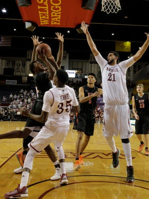 Lee Moore finds a way to penetrate the Aggies' defense and put in a basket during the first half Wednesday at the Pan American Center in Las Cruces.