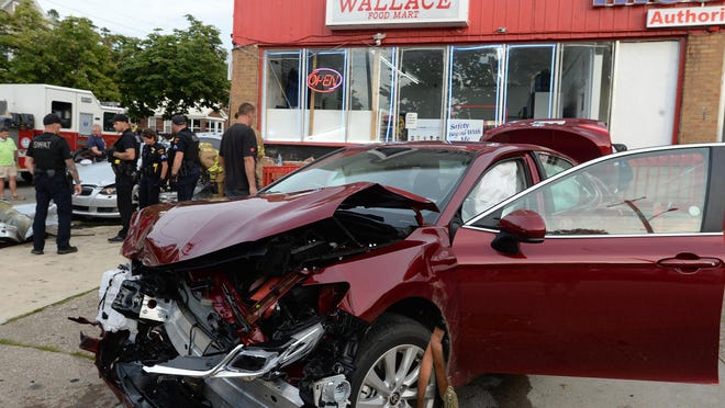 Erie police investigate a two-vehicle accident Thursday at East Sixth and Wallace streets in Erie. After impact the vehicles struck the Wallace Food Mart causing damage to the building. The driver of one of the vehicles ran from the scene but was apprehended by police.