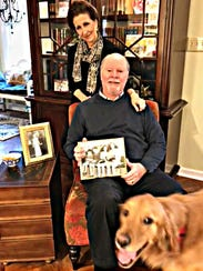 Michael and Elizabeth Grant pose with pictures of Michael's