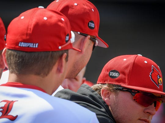 "Louisville players wear ball caps with the name ""Todd"" in memory of Todd Esser during the game between Louisville and Virginia at Jim Patterson Field on the campus of The University of Louisville, in Louisville, Ky, April 21, 2018"
