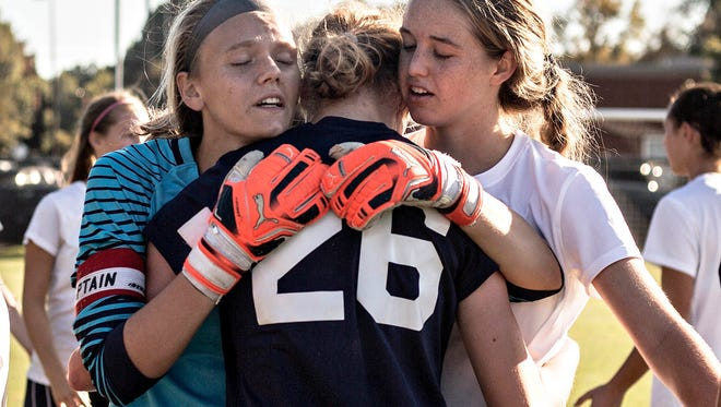 Houston seniors Kaylee Hammer (left) and Katrina Ostrom hug Arlington senior Erin Yonak after the AAA sectional game between Houston and Arlington high schools on Saturday afternoon at Houston Middle School. Houston defeated Arlington 2-1 after a goal by senior Jillian Hildreth (20). Houston will advance to the state championship.  Andrea Morales / The Commercial Appeal