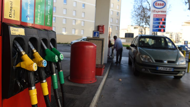 A consumer fills up his fuel tank at a gas station
