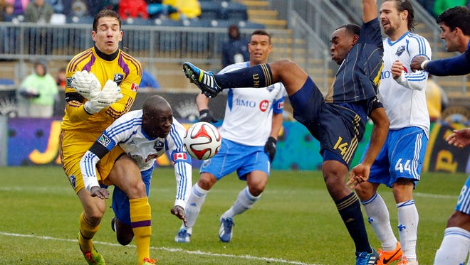 Montreal Impact defender Hassoun Camara (second from left) clears the ball as Philadelphia Union midfielder Amobi Okugo (14) tries to settle it during the first half at PPL Park.