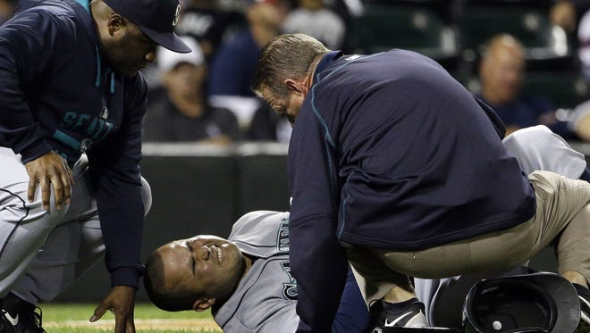 Seattle Mariners' Jesus Montero, center, reacts after fouling a ball off himself as manager Lloyd McClendon, left, and a team trainer check him during the fifth inning of a baseball game against the Chicago White Sox, Thursday, Aug. 27, 2015, in Chicago.