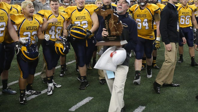 Clarkston coach Kurt Richardson carries the Division 1 state championship trophy after the 33-25 win over Saline Saturday at Ford Field.
