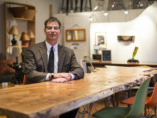 Algin owner Alan Weiss sits at a large, reclaimed wood