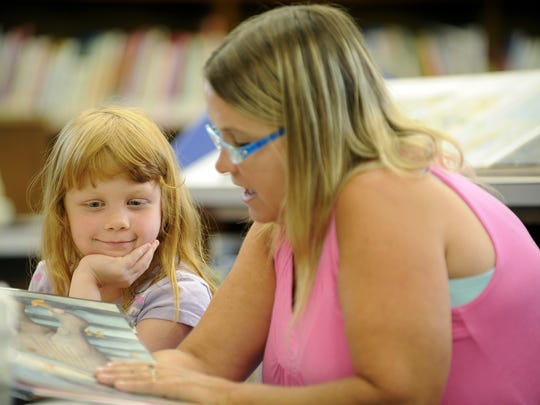 Daisy Greyer, 5, and her mother Jessie of Waynesboro read books together at the Waynesboro Public Library on Tuesday, July 21, 2009.