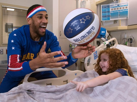 Harlem Globetrotter, Zeus McClurkin, teaches Brooklyn Aribian, right, how to spin a basketball on her finger during his visit to The Studer Family Children's Hospital at Sacred Heart  Monday, Feb. 5, 2018.